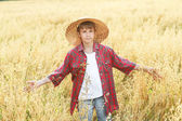 Portrait of walking teenage boy in yellow wide-brimmed natural straw hat — Stock Photo