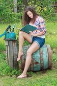 Barefoot brunette girl sitting on old vintage blue wooden barrel with book — Stock Photo