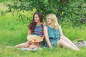 Blonde and brunette girls sitting with organic farming harvest — Stock Photo