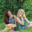 Two girls sitting on garden grass under tree branch with apples — Stock Photo #70181013