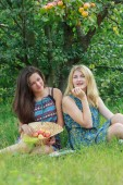 Two girls sitting on garden grass under tree branch with apples — Stock Photo