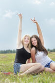 Two college friends on summer vacations showing signs of the horns — Stock Photo