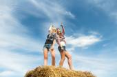 Two girls dancing in full length on straw bale — Stock Photo