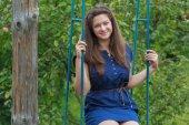 Portrait of brunette girl in navy blue sundress sitting on handmade swing — Stock Photo