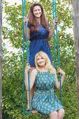 Young girls on handmade swing in summer apple trees garden — Stock Photo