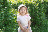 Two year-old laughing girl in corduroy flat cap at green garden shrubbery background — Stock Photo