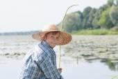 Angling teenage boy with handmade green twig fishing rod is looking back — Foto Stock