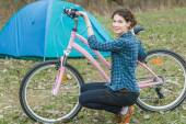 Brunette girl is sitting near pink bike during her bicycle touring — Stock Photo