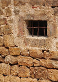 Small grilled window in a stone wall — Stock Photo