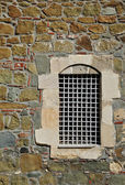 Barred window in the stone wall — Stock Photo