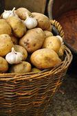 Garlic and potatoes in basket — Stock Photo