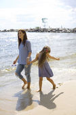 Mother and daughter walking along the seashore — Stock Photo