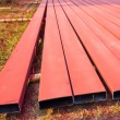 Steelworks sprayed in red with spray gun on the ground  — Stock Photo #62034307