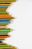 Colorful pencils on the white paper, view from above — Stock Photo