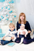Mommy with children at New Year tree — Stock Photo