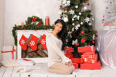 Young brunette woman in christmas interior — Stock Photo