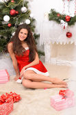 Pretty woman in red in Christmas interior — Stok fotoğraf