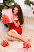 Pretty woman with gift in Christmas interior — Stok fotoğraf