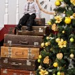 Boy on pile of suitcases at christmas tree — Stock Photo #58679571