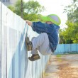 Little boy climbing fence outdoors — Stock Photo #68542887