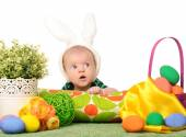 Baby with easter colored eggs — Photo