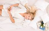 Pretty blonde lady with cup of coffee in bed — Foto de Stock