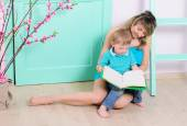 Mom and son reading book indoors — Stock Photo