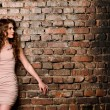 Sensual woman on old brick wall background — Stock Photo #73707197