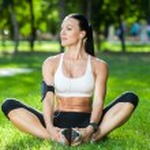 Yoga woman on green grass in lotus pose — Stock Photo #56647249
