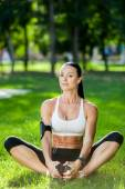Yoga woman on green grass in lotus pose — Stock Photo