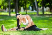 Beautiful sport woman doing stretching fitness exercise in city park at green grass. Yoga postures — Stock Photo