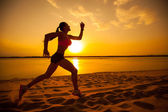 Woman running alone at beautiful sunset in the beach. Summer sport and freedom concept. — Stock Photo
