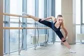 In the hall girl doing stretching near Barre — Zdjęcie stockowe