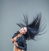 Beautiful girl exy breasts in unbuttoned jacket with long black hair, developing hair — Stock Photo