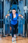 Young attractive woman training with htrx fitness straps in the gyms studio — Stock Photo
