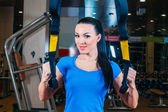 Young attractive woman training with htrx fitness straps in the gyms studio — Foto de Stock