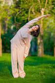 Cvičení jógy v noci, s pozadím stromy — Stock fotografie