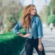 Beautiful young Caucasian girl with curly hair outdoors — Stock Photo #72374491