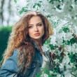 Beautiful young Caucasian girl with curly hair outdoors — Stock Photo #72374511