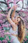 Krásná mladá žena s nádherný kudrnatý veletrhu venku, květu — Stock fotografie