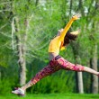 Young beautiful girl doing gymnastic jumps outdoors — Stock Photo #72525093