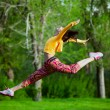 Young beautiful girl doing gymnastic jumps outdoors — Stock Photo #72525103