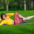 Exercising fitness woman sit ups outside during crossfit exercise training. Happy fit girl doing side crunches with elevated legs while smiling happy. — Stock Photo #72525201