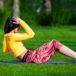 Exercising fitness woman sit ups outside during crossfit exercise training. Happy fit girl doing side crunches with elevated legs while smiling happy. — Stock Photo #72525219