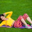 Exercising fitness woman sit ups outside during crossfit exercise training. Happy fit girl doing side crunches with elevated legs while smiling happy. — Stock Photo #72525231