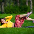 Exercising fitness woman sit ups outside during crossfit exercise training. Happy fit girl doing side crunches with elevated legs while smiling happy. — Stock Photo #72525247