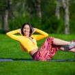 Exercising fitness woman sit ups outside during crossfit exercise training. Happy fit girl doing side crunches with elevated legs while smiling happy. — Stock Photo #72525261