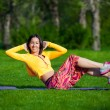 Exercising fitness woman sit ups outside during crossfit exercise training. Happy fit girl doing side crunches with elevated legs while smiling happy. — Stock Photo #72525277