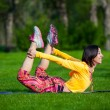 Pretty woman doing yoga exercises in the park — Stock Photo #72525301
