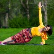 Pretty woman doing yoga exercises in the park — Stock Photo #72525311
